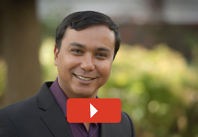 Head shot of Asim with play button overlaid.
