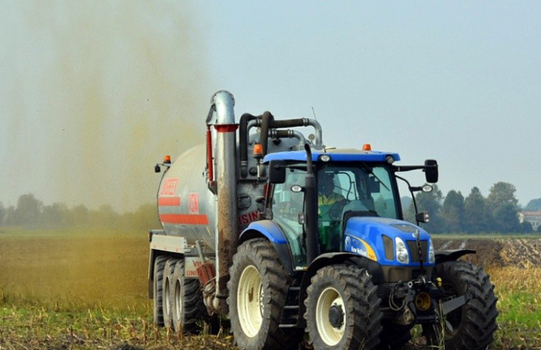 Tractor distributing liquid manure on a field